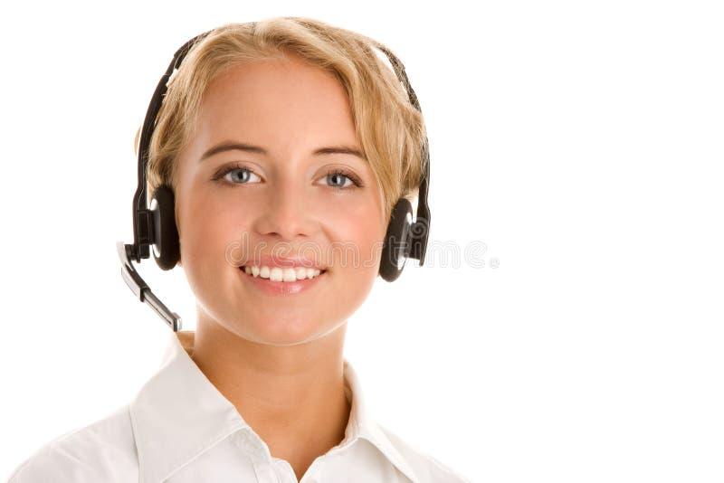 Bärande hörlurar med mikrofon för ung receptionist arkivfoto