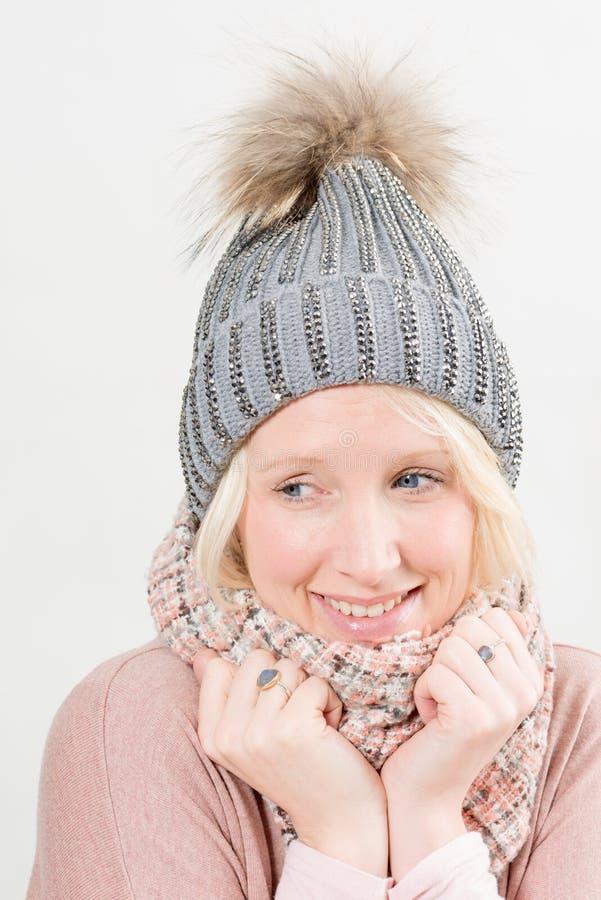 Bärande halsduk för kvinna och vinterhätta som bort ser royaltyfri bild