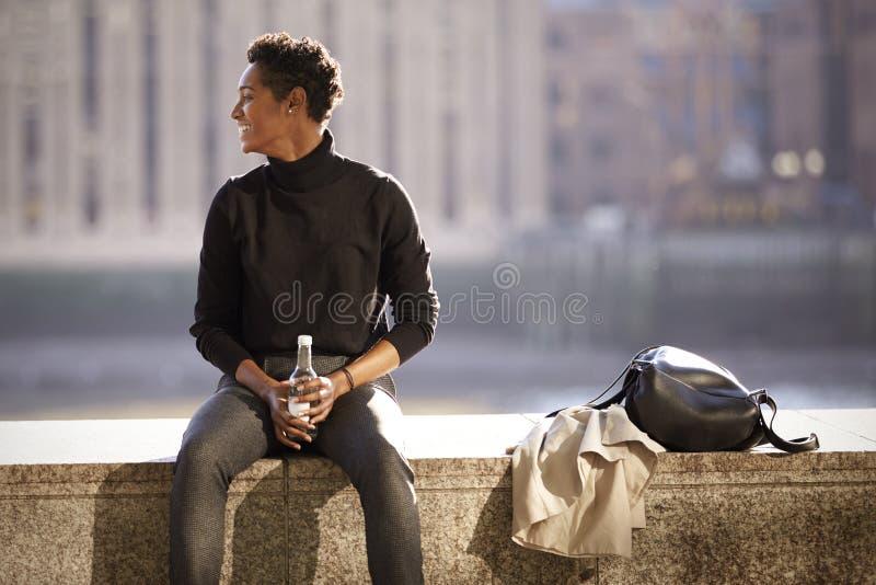 Bärande halvpolokragetröja för ung svart kvinna som sitter i solen på en invallningvägg vid flodThemsen i London som är bakbelyst arkivfoton