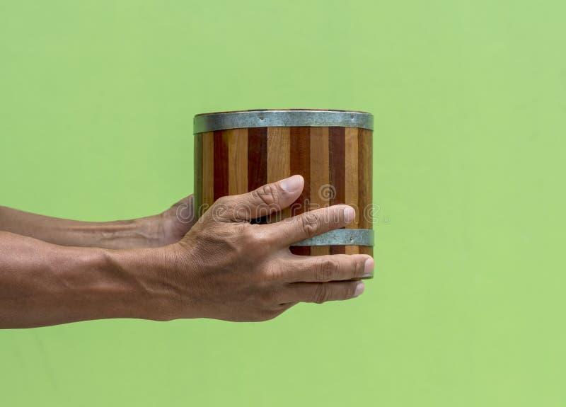 Bärande hand för forntida trähink med den gröna väggen royaltyfria bilder