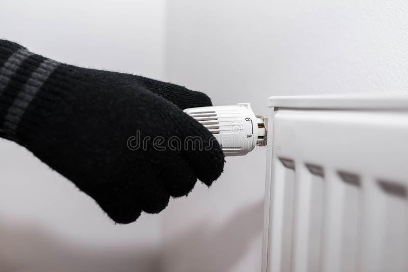 Bärande handskar för man som justerar knoppen för elementvärmekontrollant royaltyfria foton