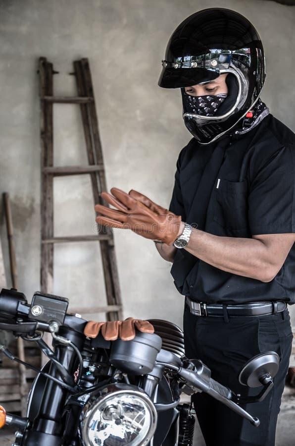 Bärande handske för ung man för att rida motorcykeln royaltyfri bild
