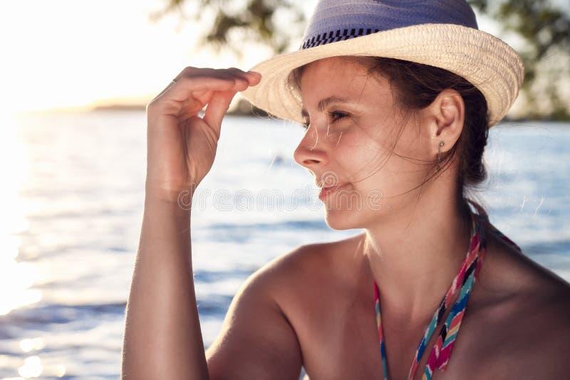Bärande hatt för attraktiv brunbränd sexig gullig dam på stranden på solnedgången på en varm sommarafton drömlik behagfull kvinna fotografering för bildbyråer