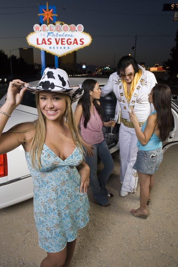 Bärande hatt för kvinna med vänner och Elvis Presley Impersonator In The Background arkivfoto