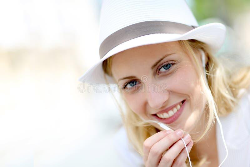 Bärande hatt för ung härlig kvinna med hörlurar arkivbild