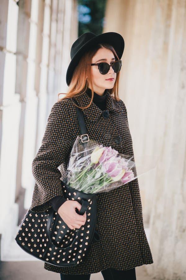 Bärande hatt för ung härlig modekvinna som går på gator för en stad med blommor royaltyfria foton