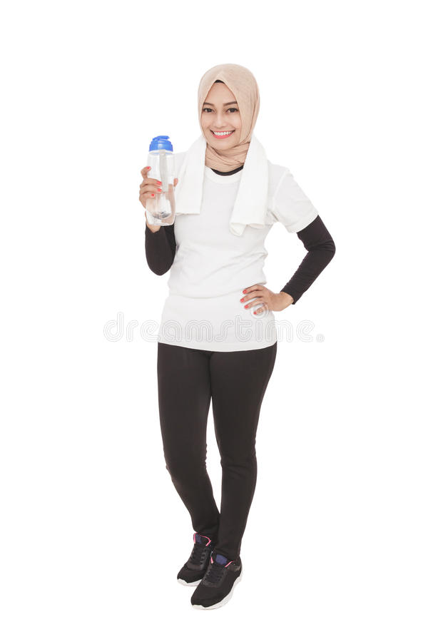 Bärande hijab för asiatisk sportig kvinna som rymmer en flaska av mineralisk wat royaltyfri bild