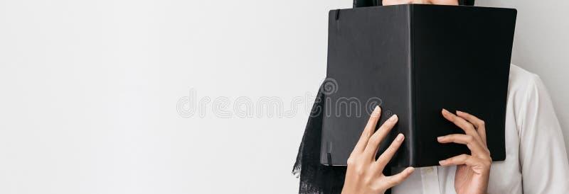 Bärande hijab för muslimsk kvinna, vit skjorta och rymma en svart räkningsbok framme av henne på rätsidan med kopieringsutrymme royaltyfria foton