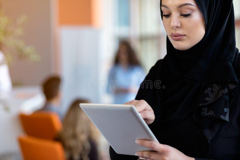 Bärande hijab för nätt kvinna framme av bärbar datorsökandet och att göra kontorsarbete, affär, finans och arbetsstationsbegrepp royaltyfri foto