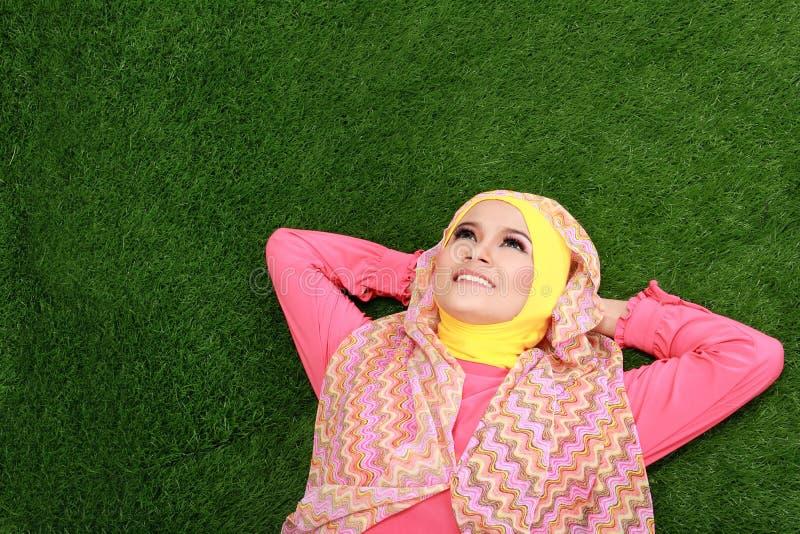 Bärande hijab för ung muslimflicka som ligger på gräs och ser upp royaltyfri fotografi