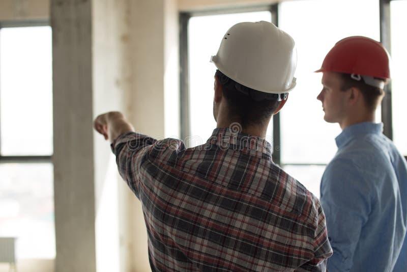 Bärande hjälm för anställd som visar stället av konstruktion till en arbetsledare royaltyfria foton