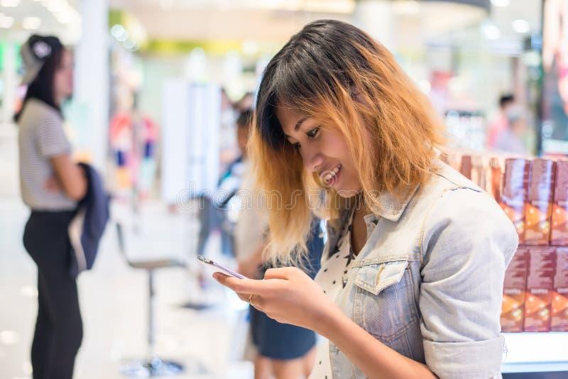 Bärande jeanomslag för ung härlig kvinna som smsar på smartphen royaltyfria bilder