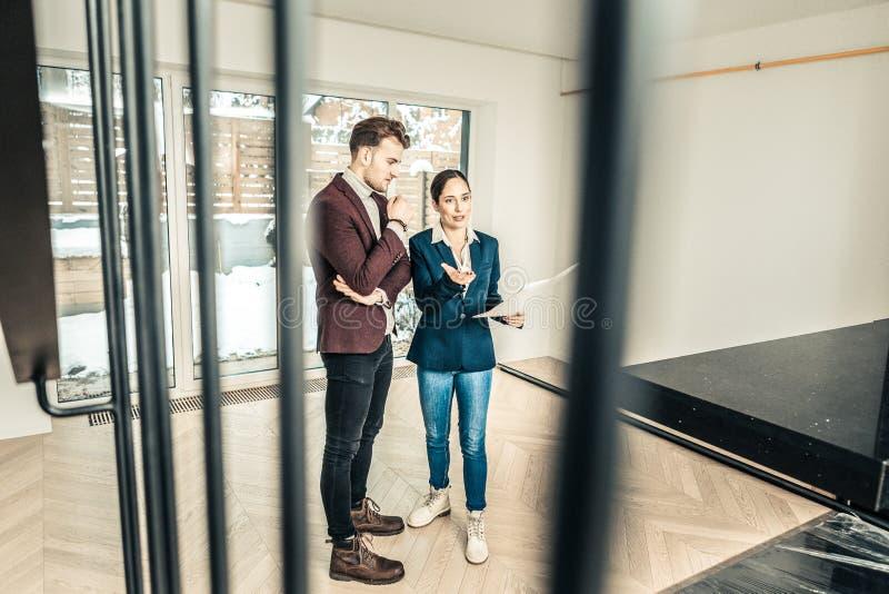 Bärande jeans för fastighetsmäklare och anseende för blått omslag i rum med klienten arkivfoto