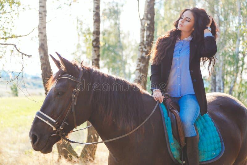 Bärande jeans för härlig sexig brunett, blus och svart omslag som rider en häst på den soliga sommardagen royaltyfria bilder