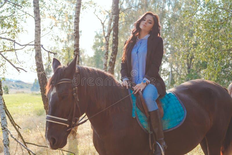 Bärande jeans för härlig sexig brunett, blus och svart omslag som rider en häst på den soliga sommardagen royaltyfri bild