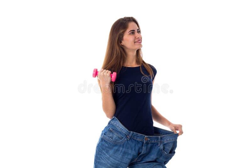 Bärande jeans för kvinna av mycket större format och innehav en hantel fotografering för bildbyråer