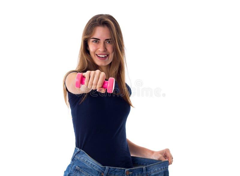 Bärande jeans för kvinna av mycket större format och innehav en hantel arkivbild