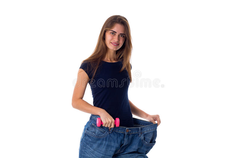 Bärande jeans för kvinna av mycket större format och innehav en hantel royaltyfria bilder