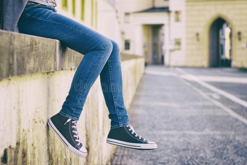 Bärande jeans för kvinna och nya gymnastikskor royaltyfri foto