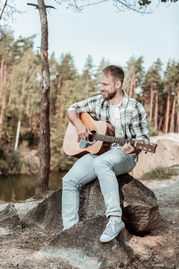 Bärande jeans för stilig skäggig man och kvadrerad skjorta som spelar gitarren nära sjön royaltyfri fotografi