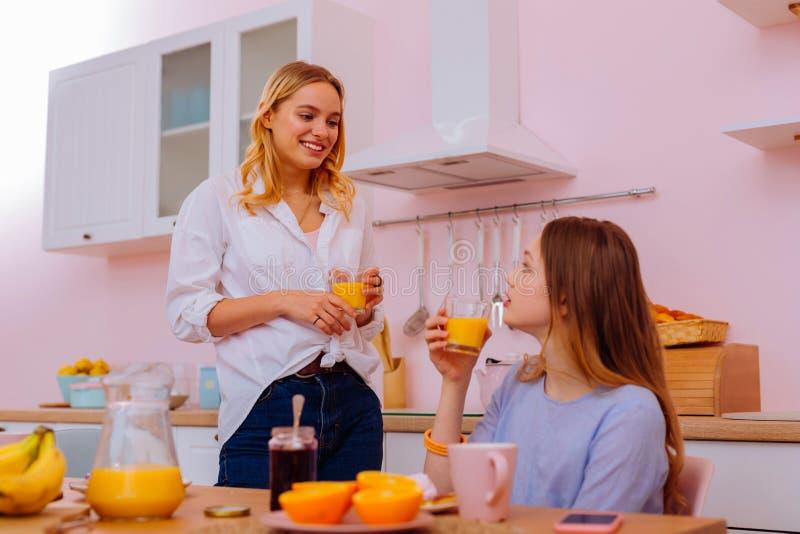 Bärande jeans och skjorta för syster som sammanfogar hennes sibling för frukost royaltyfria foton