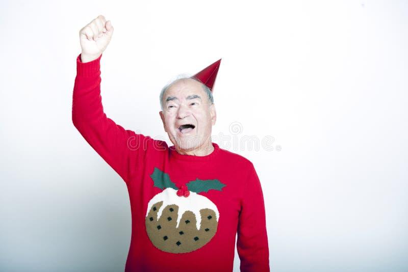 Bärande julförkläde för hög vuxen man som lyfter hans arm i luften fotografering för bildbyråer