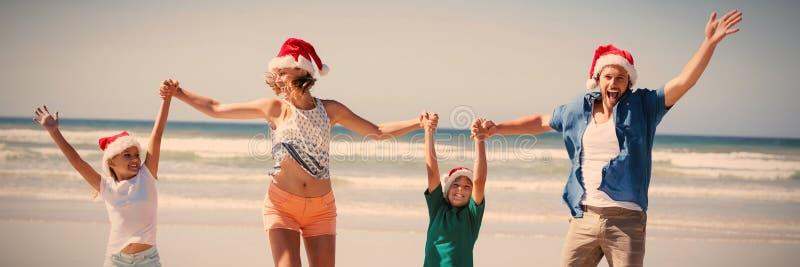 Bärande jultomtenhatt för gladlynt familj, medan hoppa på stranden royaltyfri bild