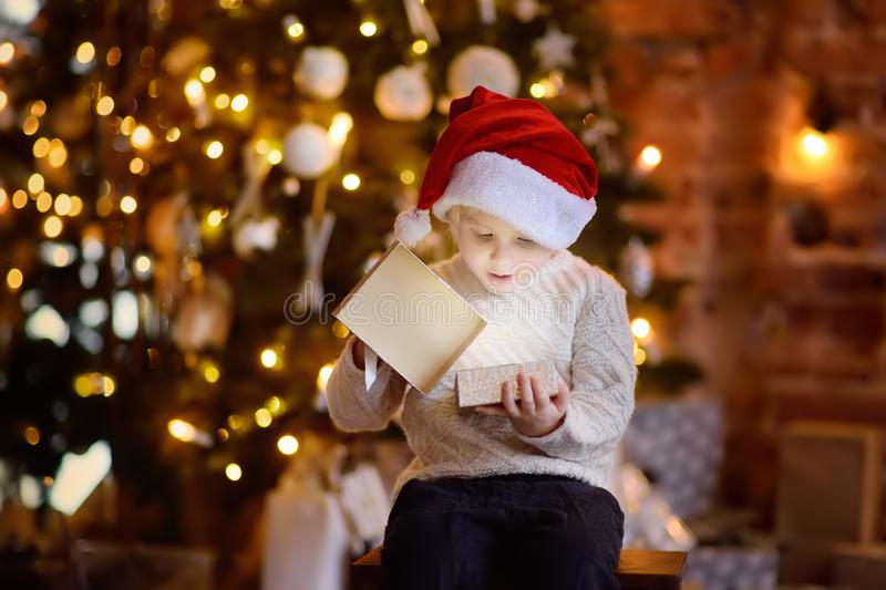 Bärande jultomtenhatt för gullig pys som öppnar en julgåva royaltyfria foton