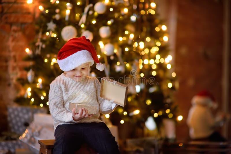 Bärande jultomtenhatt för gullig pys som öppnar en julgåva fotografering för bildbyråer