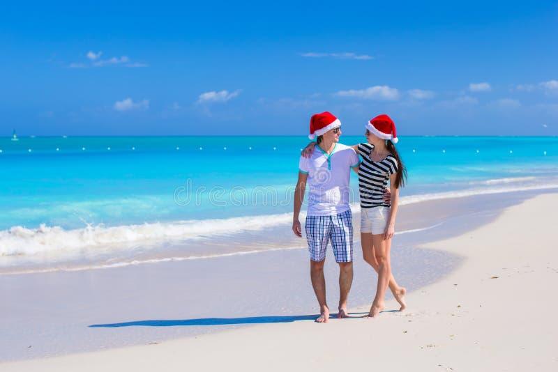 Bärande jultomtenhatt för lyckliga par på den karibiska stranden arkivbild