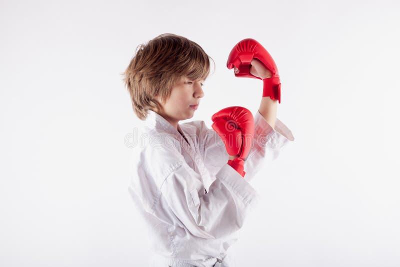 Bärande karatekimono för ung pojke och född upp concentra för boxninghandskar fotografering för bildbyråer