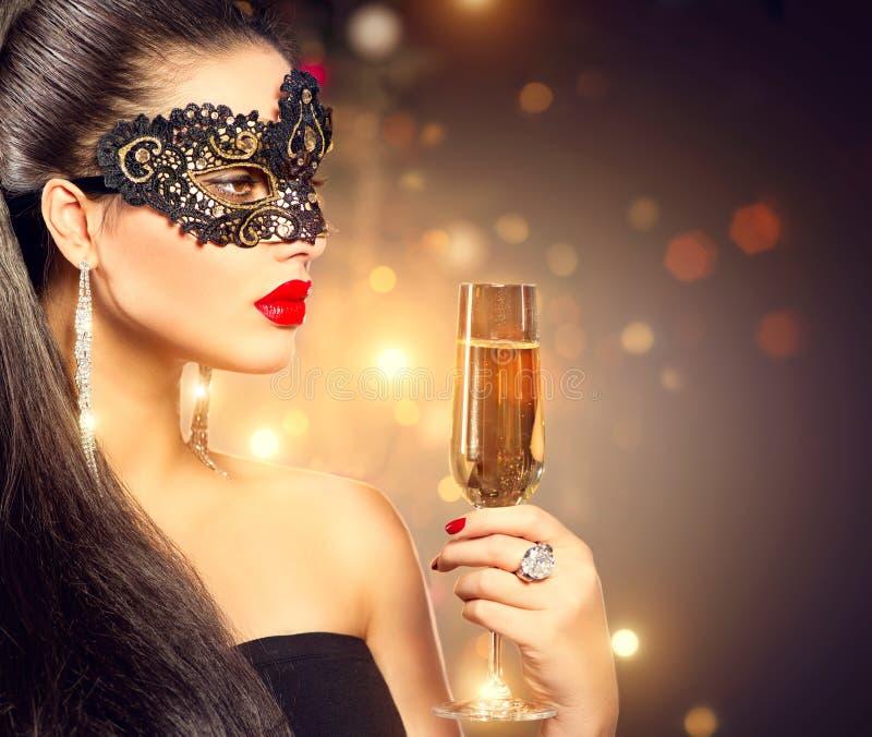 Bärande karnevalmaskering för kvinna med exponeringsglas av champagne royaltyfria bilder