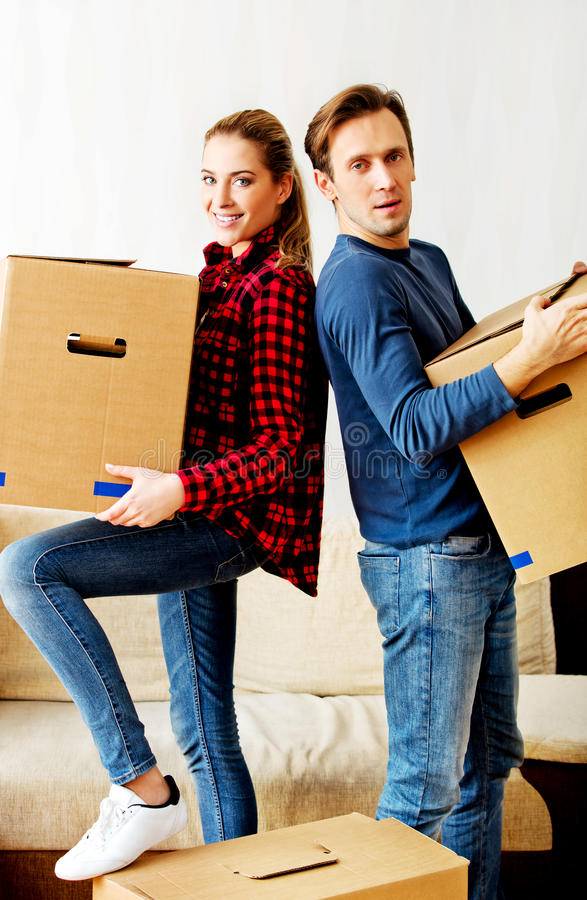 Bärande kartonger för lyckliga par i nytt hem arkivbilder