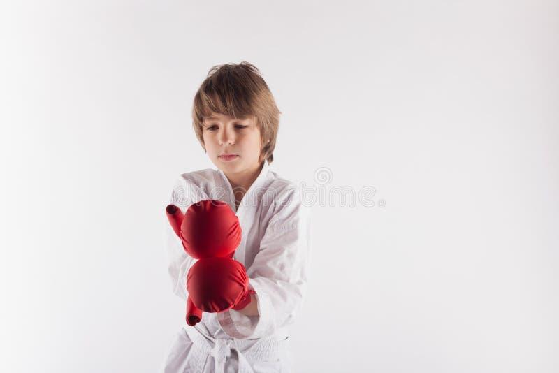 Bärande kimono för karateunge och röda boxninghandskar arkivfoto