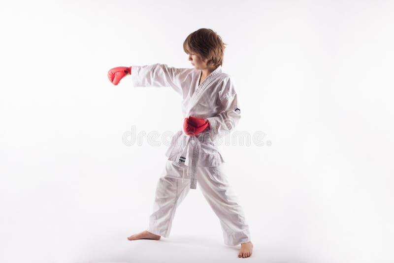 Bärande kimono för karateunge och röda boxninghandskar som gör övningar arkivfoto