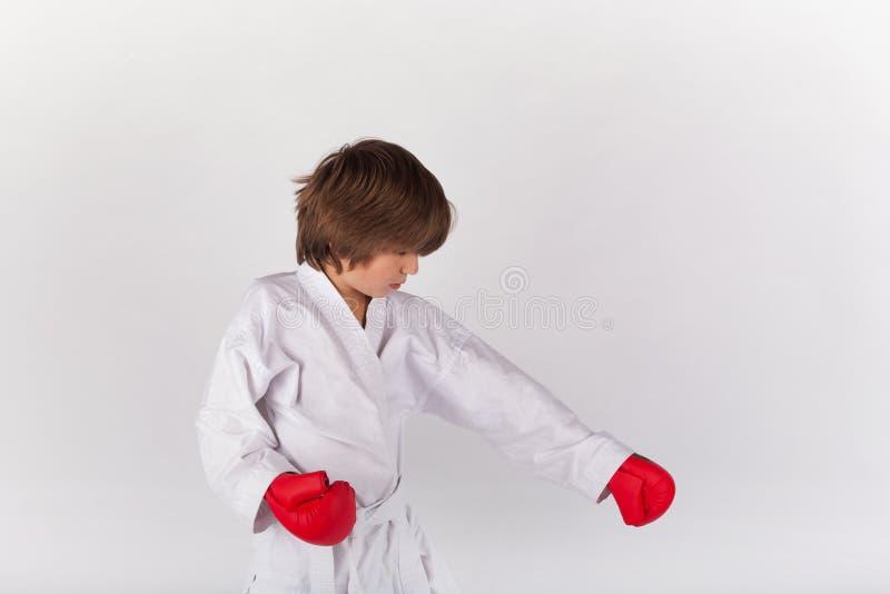 Bärande kimono för karateunge och röda handskar och öva för boxning arkivfoton