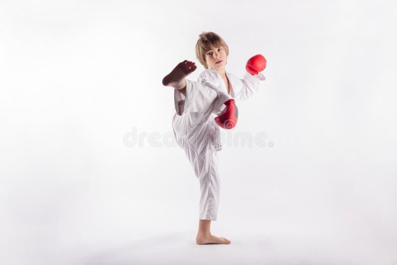 Bärande kimono för ung pojke och röda boxninghandskar som visar exercices arkivfoton