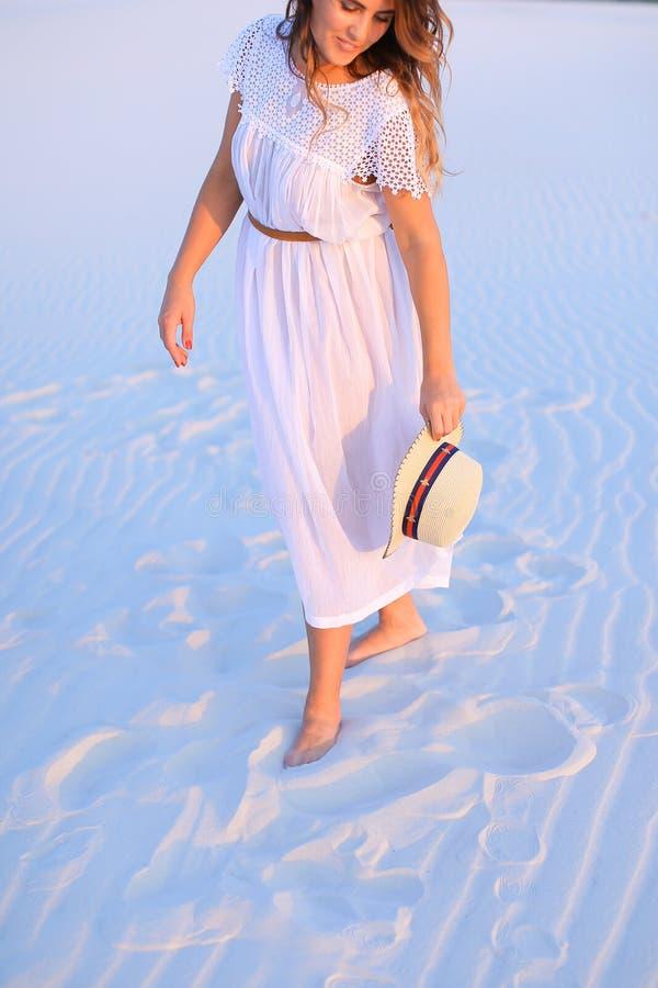 Bärande klänning- och hattanseende för ung dam på vit sand i blått royaltyfria bilder