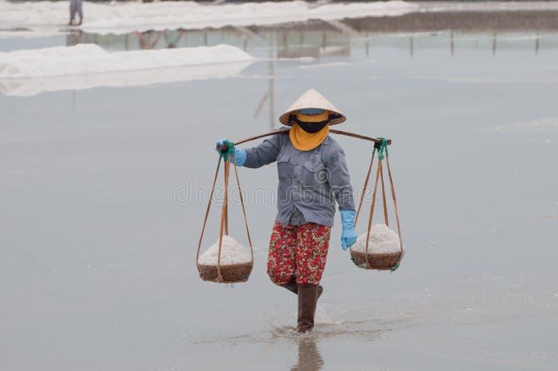 Bärande korgar för vietnamesisk kvinna med salt fotografering för bildbyråer