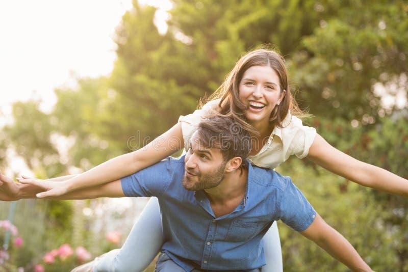 Bärande kvinna för lycklig man på baksida arkivbild
