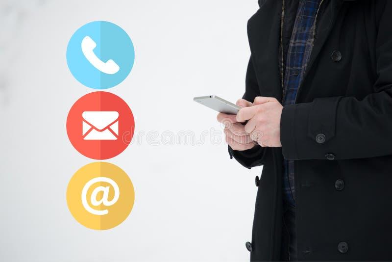 Bärande lag för man som rymmer en smartphonemobil, på en kall vinterdag för snö Med kontakten oss appell- och emailsymboler, kund royaltyfri fotografi