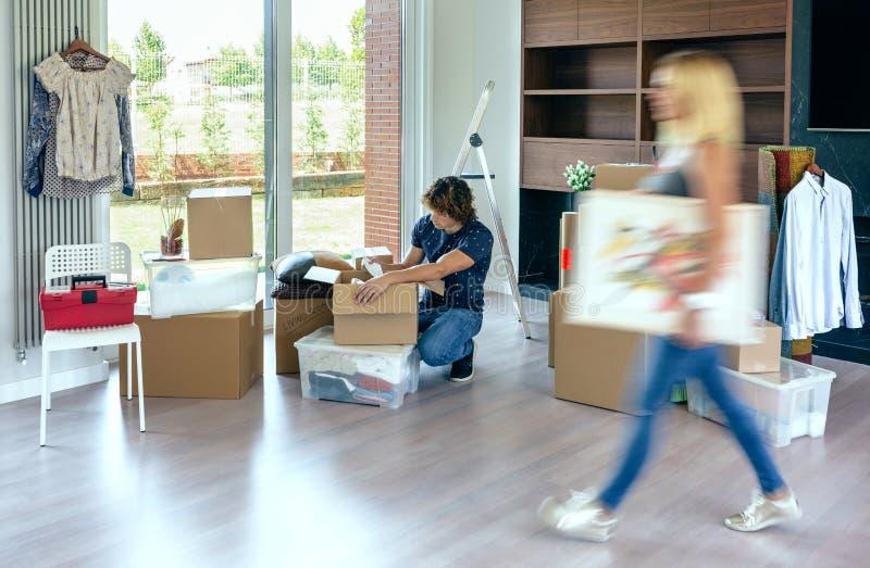 Bärande målning för kvinna, medan maken packar upp royaltyfri bild