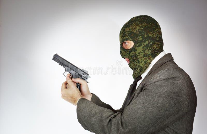 Bärande maskering för mördare med ett vapen royaltyfri foto