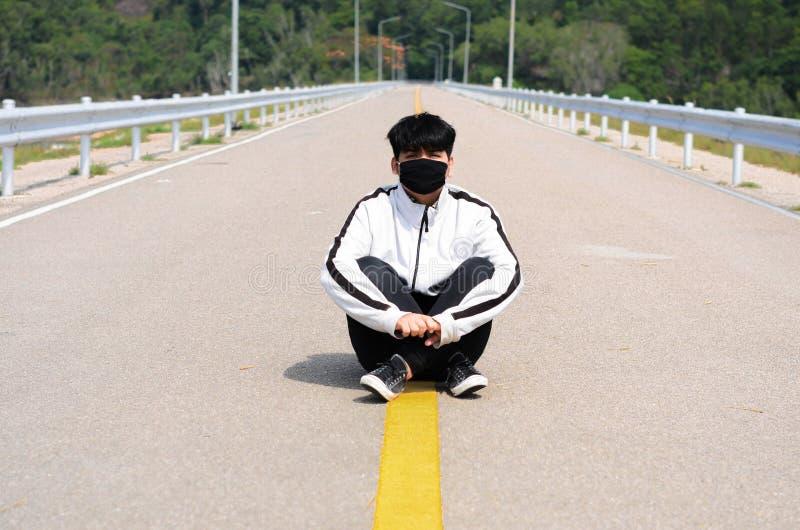 Bärande maskering för pojke att koppla av på vägen, når att ha joggat fotografering för bildbyråer