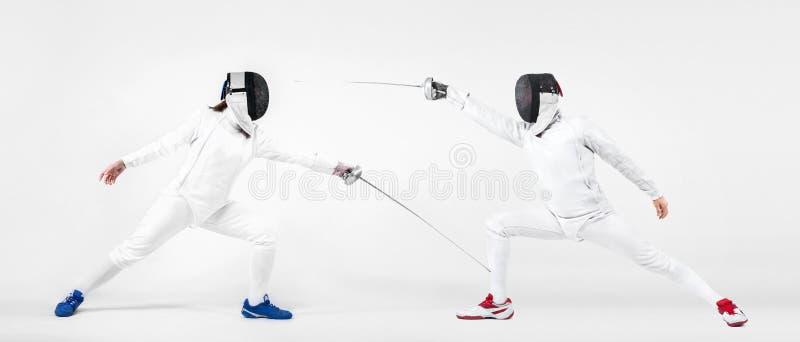 Bärande maskering för ung fäktareidrottsman nen och vitfäktningdräkt rymma svärdet bakgrund isolerad white royaltyfri bild