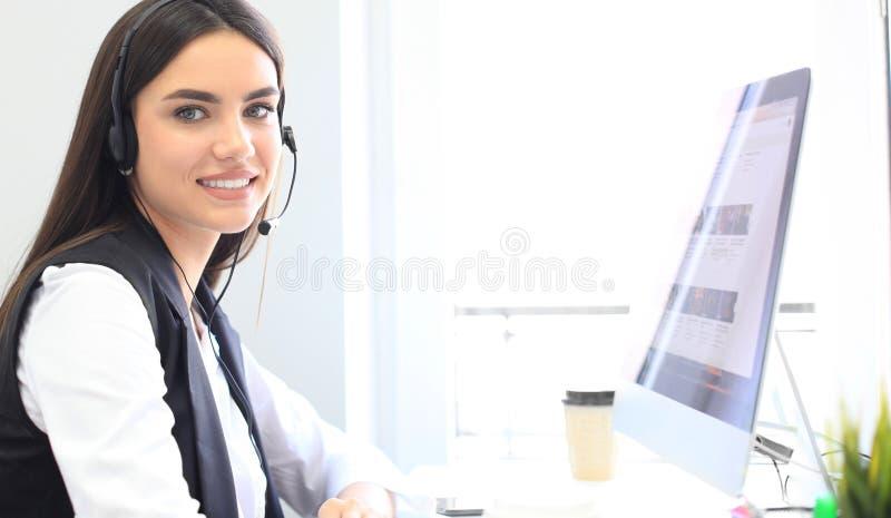 Bärande mikrofonhörlurar med mikrofon för affärskvinna genom att använda datoren i kontoret - operatör, appellmitt royaltyfri fotografi