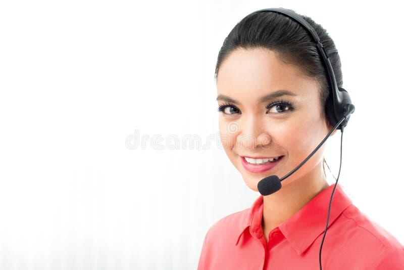 Bärande mikrofonhörlurar med mikrofon för kvinna som en operatörs- eller appellmitt arkivbilder
