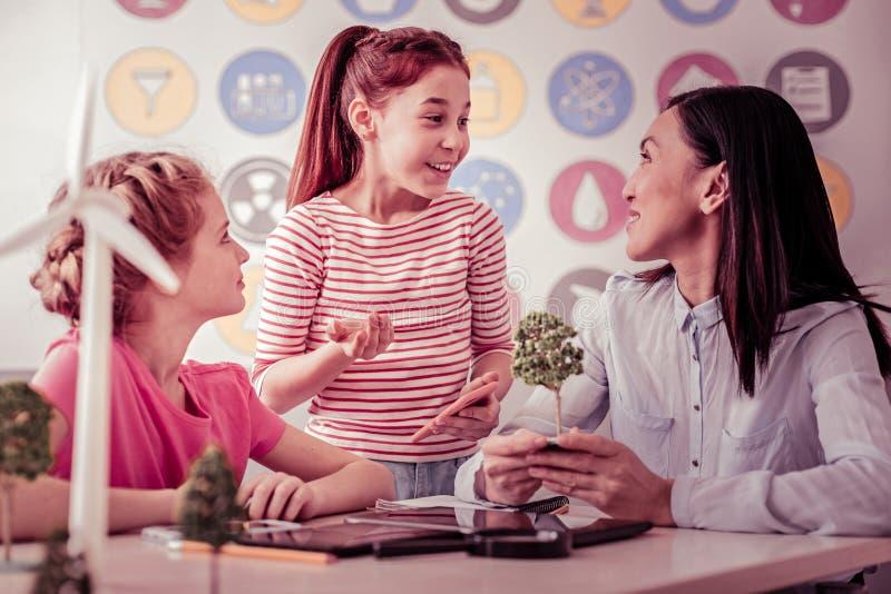Bärande mobiltelefon för ung ljust rödbrun flicka och samtal expressively fotografering för bildbyråer