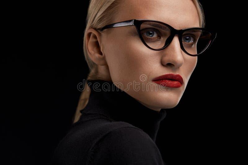 Bärande modeexponeringsglas för kvinna Kvinnlig med röda kanter i Eyewear royaltyfri foto