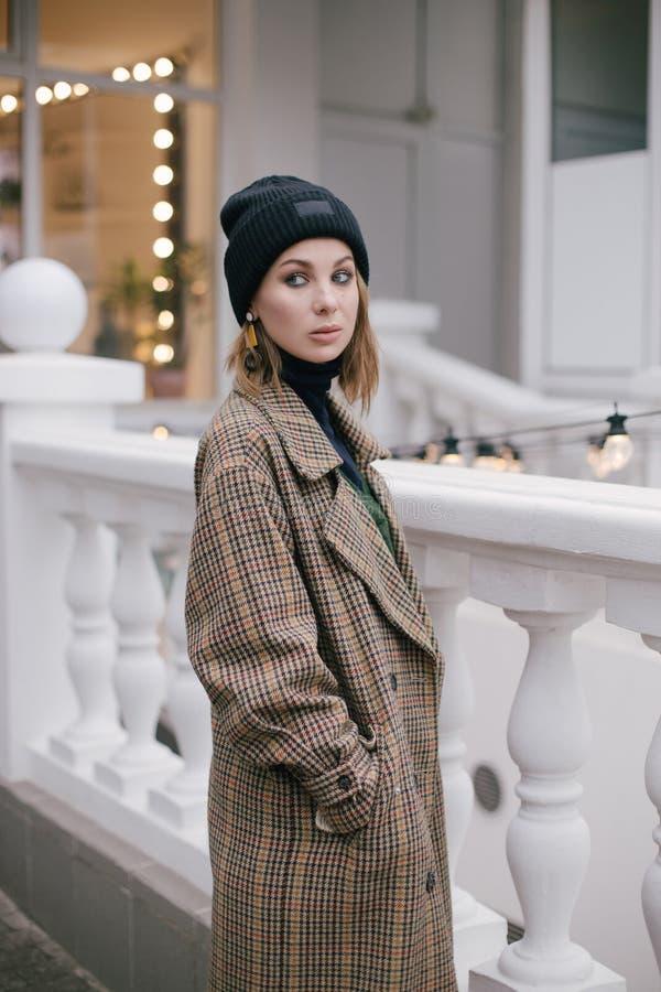 Bärande modekläder för ung härlig kvinna som poserar på gatan arkivbild